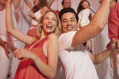 Stock Photo of Germany, Stuttgart, Group of people dancing in nightclub, smiling