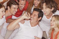 Germany, Stuttgart, Man singing karaoke with his friends in nightclub - stock photo