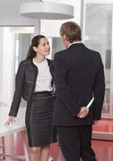 Businessman talking to woman and holding knife behind his back - stock photo