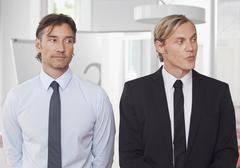 Stock Photo of Two businessmen standing with distrust expression