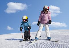 Switzerland, Boy and girl skiing in snow Stock Photos
