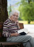 Stock Photo of Austria, Senior woman sitting on bench and reading book