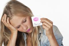 Teenage girl holding a piece of paper with lipstick imprint Stock Photos
