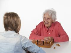 Senior woman and teenage girl playing Fox And Hen Game, smiling Stock Photos