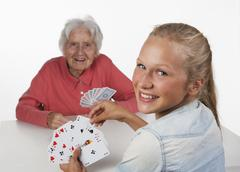 Senior woman and teenage girl playing cards, smiling - stock photo