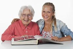 Vanhempi nainen ja teini-ikäinen tyttö katsomassa valokuva-albumi, hymyilee Kuvituskuvat