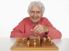 Portrait of senior woman playing Fox And Hen Game, smiling Stock Photos