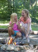 Austria, Friends preparing barbecue on camp fire - stock photo