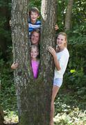 Stock Photo of Austria, Portrait of friends standing behind tree trunk, smiling
