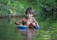 Austria, Boy bathing in stream Stock Photos