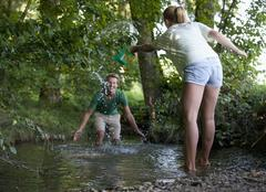 Austria, Teenage girl and boy splashing water in stream - stock photo