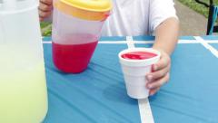 Boy serving red drink at refreshment stand Stock Footage