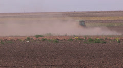 Tractor plowing in blowing dust 1 Stock Footage