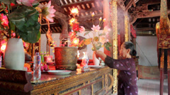 Woman burning incense in the temple god Stock Footage