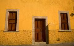 yellow adobe house brown doors morelia mexico - stock photo
