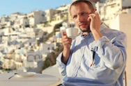 Stock Video Footage of Man talking on cellphone and drink coffee in cafe on Santorini NTSC