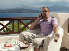 Man talking on cellphone and drinking frappe on beautiful terrace NTSC Stock Footage