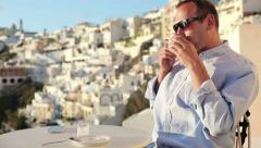 Young wealthy man drinking coffee in cafe on Santorini HD Stock Footage