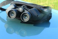 Binoculars in the pouch on the hood of the car. Stock Photos