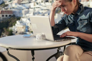 Stock Video Footage of Worried woman working on laptop in cafe on Santorini NTSC