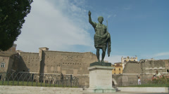 Two women walk past Caesar statue in Rome (slomo dolly) Stock Footage