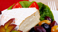 aged camembert cheese on green salad - stock footage