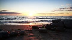 Ocean waves at sunset with smooth rocks on the sand. Dolly shot. Stock Footage