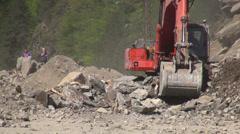 Excavator cleaning up rocks after fresh landslide, Georgia, Caucasus Stock Footage