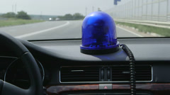 Driving car with blue flashing light on highway Stock Footage