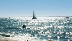 Sailing boat and man swimming in the ocean, France Stock Footage