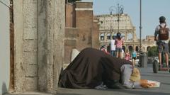 A Roman begger near Colosseum in Rome 4 (slomo dolly) Stock Footage