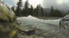Fast Flowing Stream Passes Camera with Frequent Surges over Lens Stock Footage