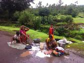 Indian women wash clothes on roadside Stock Photos