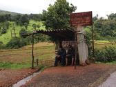 Indian men waiting for bus in tin shack Stock Photos