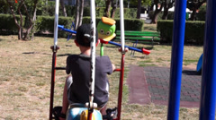 Unidentified kids on a swing Stock Footage