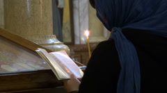 Woman reading, candle, church, Tbilisi Stock Footage