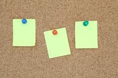 Stock Photo of three yellow memo sticker on notice cork board