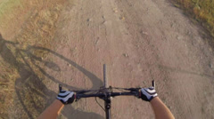 Riding mountain bike overtaking his shadow - stock footage