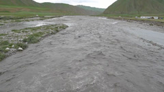 Muddy flood river from glaciers of snow mountains, Qinghai, China Stock Footage