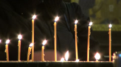 Praying behind candles in a church in Tbilisi Stock Footage