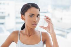 Serious model using her asthma atomizer - stock photo