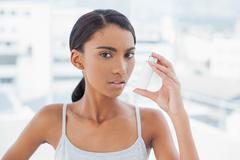 Serious model using her asthma atomizer Stock Photos
