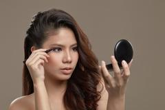 Female asian applying eye liner Stock Photos
