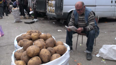 Reading magazine, selling potatoes, market, Tbilisi, Georgia Stock Footage