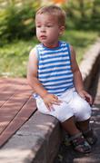 Cute boy sitting on the curb - stock photo