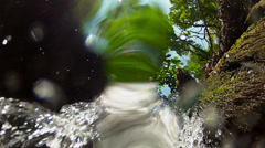Camera under the waterfall looking upwards, slow motion Stock Footage