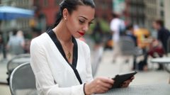 Beautiful woman using ipad tablet computer outdoor cafe Stock Footage