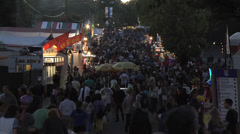 Crowd at country fair, time lapse fast, late evening along midway. Stock Footage