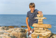 boy building inukshuk - stock photo