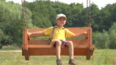 Little boy riding a wooden swing, Slow Motion 1 Stock Footage